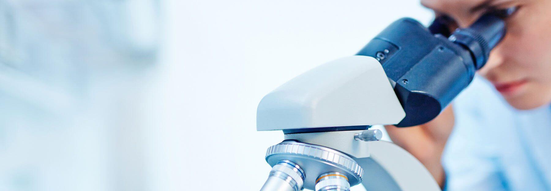 Frau schaut in Mikroskop
